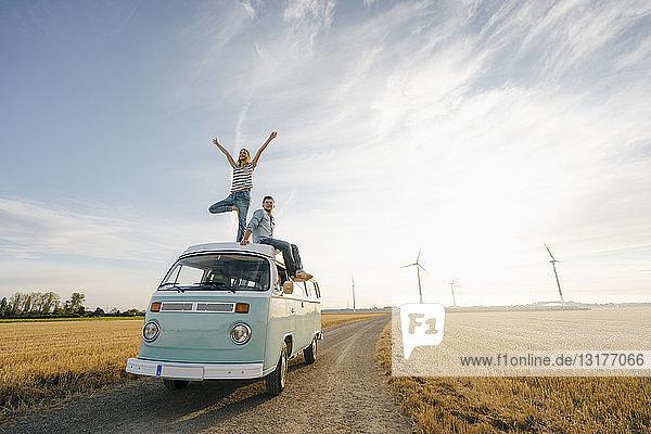 Junges Paar auf dem Dach eines Wohnmobils in ländlicher Landschaft