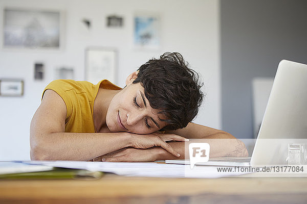 Woman at home resting on table with laptop