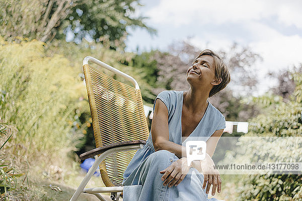 Relaxed woman sitting in garden on chair with closed eyes