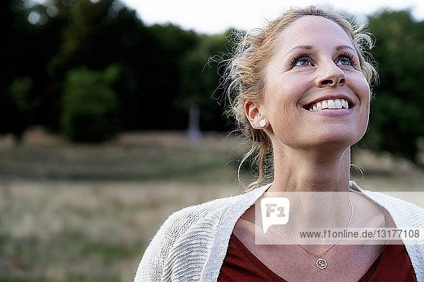 Porträt einer lächelnden Frau in der Natur beim Aufblicken