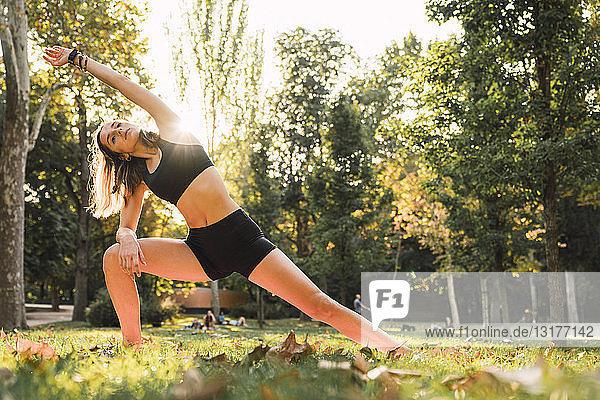 Fitte junge Frau  die in einem Park Yoga praktiziert