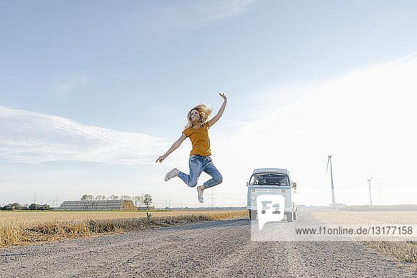 Überschwängliche junge Frau springt auf Feldweg bei Wohnmobil in ländlicher Landschaft