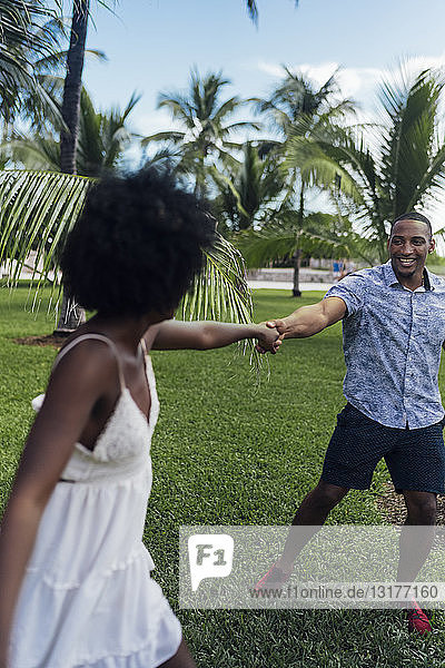 USA  Florida  Miami Beach  happy young couple dancing in a park in summer