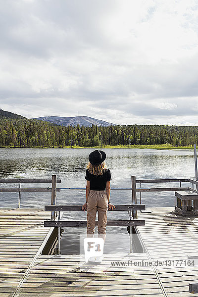 Finland  Lapland  woman wearing a hat standing on jetty at a lake