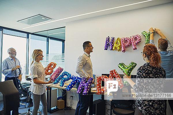 Kollegen schmücken Büro mit Glückwunschschreiben