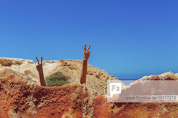 Frau macht Siegeszeichen hinter Felsen am Strand