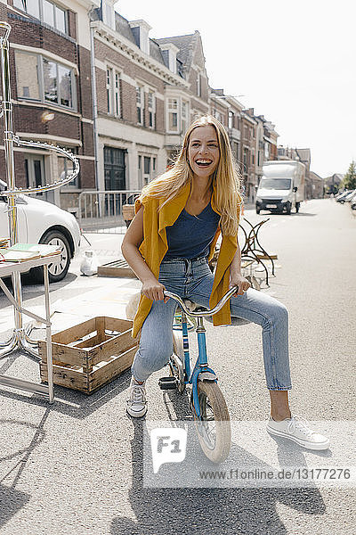 Belgien  Tongeren  glückliche junge Frau auf einem Kinderfahrrad auf einem Antiquitäten-Flohmarkt