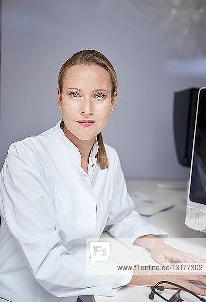 Porträt einer am Schreibtisch sitzenden Ärztin