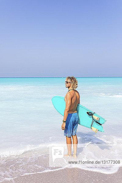 Junger Mann steht am Meer und hält sein Surfbrett