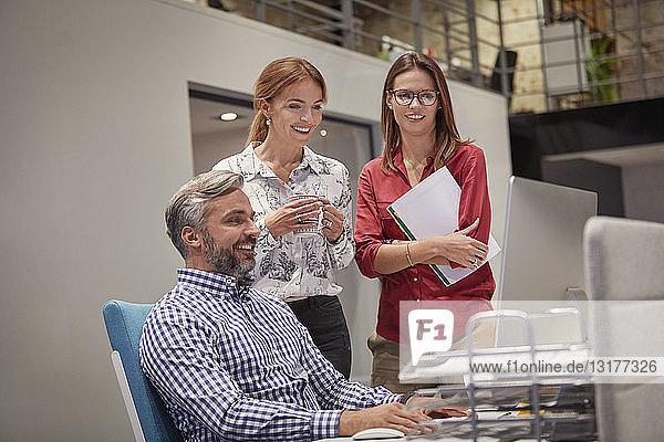 Kollegen im Gespräch vor dem PC