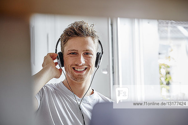 Portrait of smiling young man at home listening to music with headphones