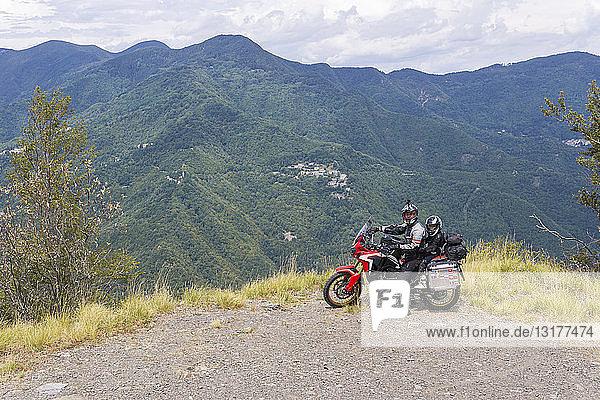 Italien  Toskana  Pistoia  Vater und Sohn machen während einer Motorradtour eine Pause am Aussichtspunkt