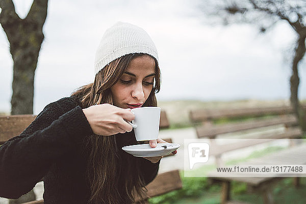 Portrait of young woman drinking cup of coffee outdoors