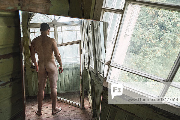 Mirror image of naked man standing at window of abandoned house