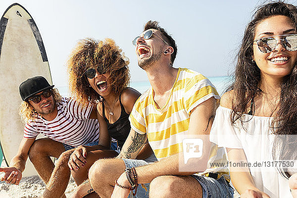 Freunde sitzen am Strand und haben Spaß