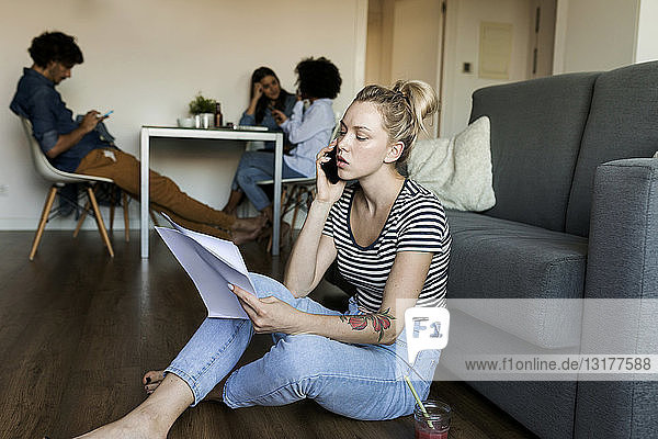 Junge Frau sitzt auf dem Boden mit Handy und Papieren und Freunden im Hintergrund