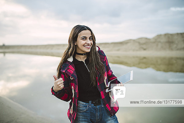 Portrait of smiling young woman taking selfie with smartphone on the beach