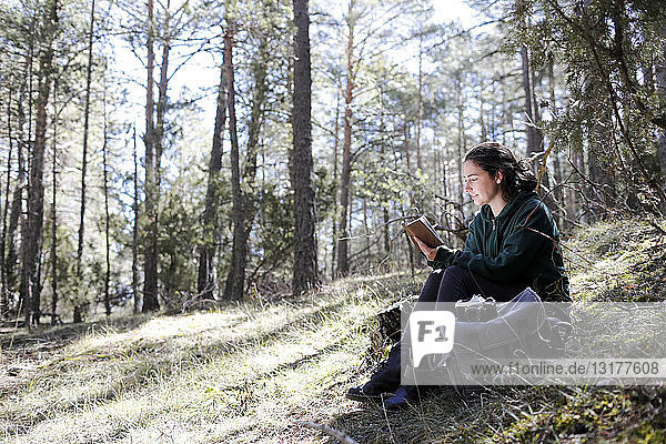 Young woman with yellow sweater in the forest  writing