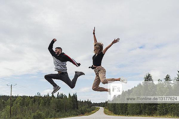 Finnland  Lappland  ausgelassenes junges Paar springt in ländlicher Landschaft