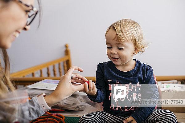 Mutter verschenkt Modeaccessoires an kleine Tochter zu Hause