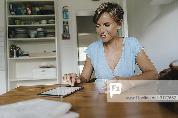 Frau sitzt zu Hause am Tisch mit Tasse Kaffee und Tablette
