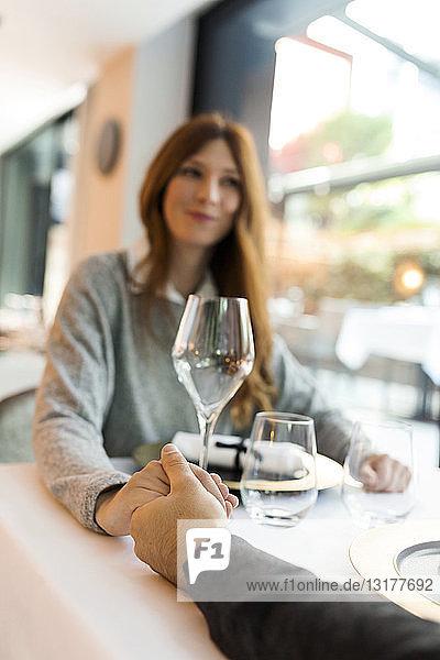 Frau hält in einem Restaurant mit einem Mann Händchen