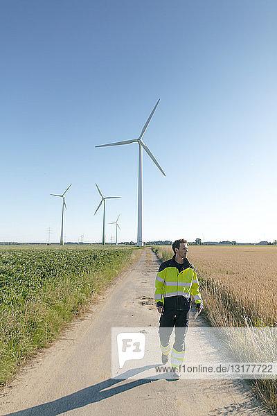 Ingenieur zu Fuß auf einem Feldweg bei einem Windpark