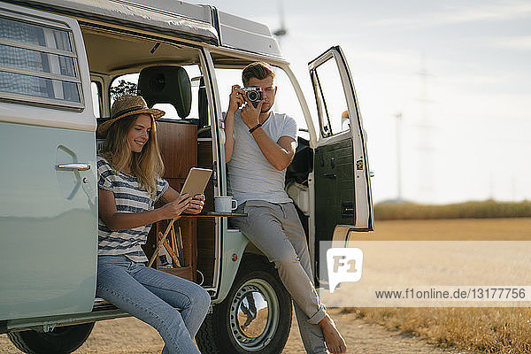 Young couple with tablet and camera at camper van in rural landscape