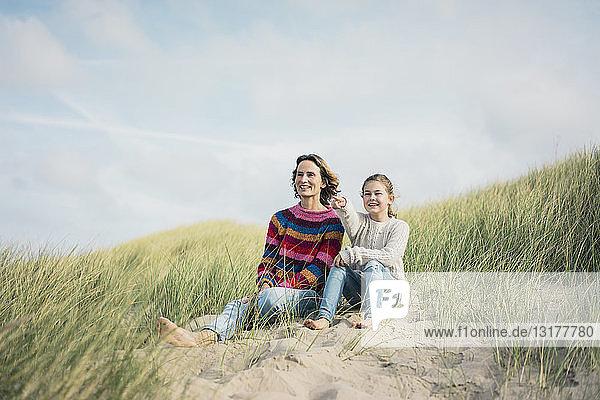 Mutter und Tochter sitzen auf einer Stranddüne  das Mädchen zeigt in die Ferne und lächelt
