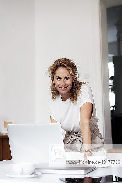 Porträt einer zufriedenen Geschäftsfrau mit Laptop