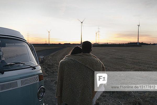 In eine Decke gehülltes Ehepaar im Wohnmobil in ländlicher Landschaft mit Windturbinen im Hintergrund