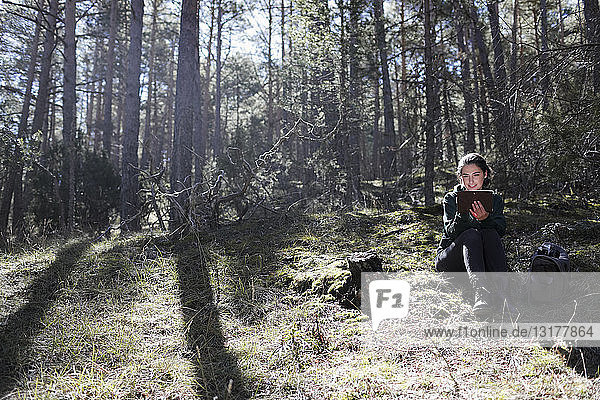 Junge Frau sitzt im Wald und schreibt