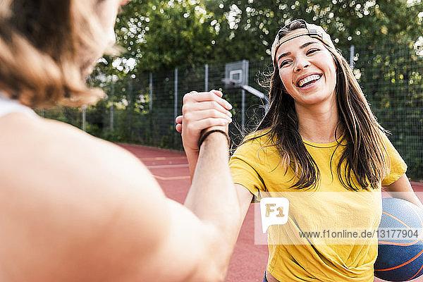 Junger Mann und junge Frau geben nach Basketballspiel ein High-Five