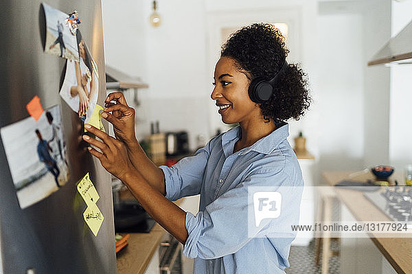Woman in her kitchen in the morning  posting sticky notes on the fridge