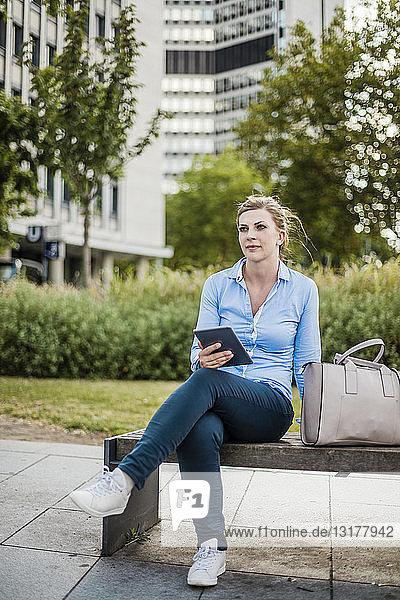 Frau sitzt auf einer Bank und hält ein Tablett