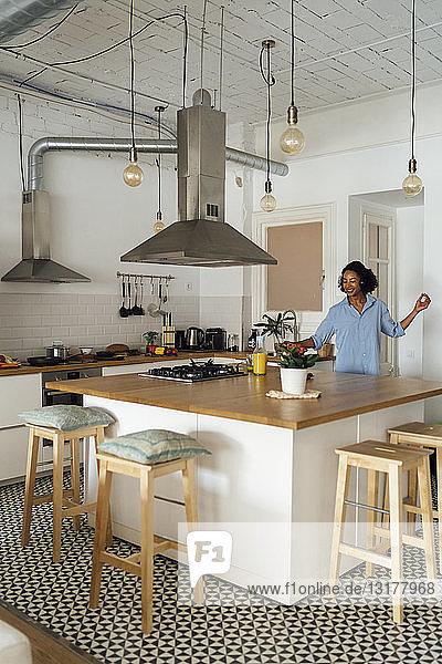 Woman having a healthy breakfast in her kitchen  listening music