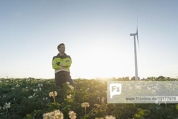 Ingenieur  der in einem Feld an einer Windkraftanlage steht