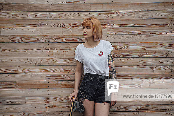 Young woman standing at wooden wall with skateboard