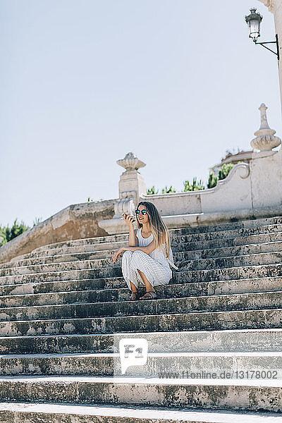 Spanien  Valencia  Frau sitzt auf einer Treppe und benutzt ein Smartphone