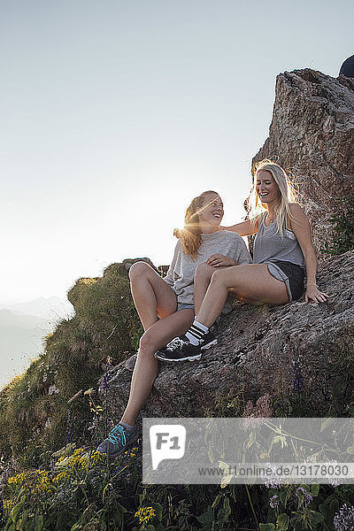 Switzerland  Grosser Mythen  two happy girlfriends on a hiking trip having a break at sunrise
