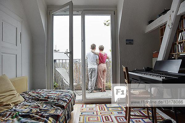 Rückansicht eines Paares  das zu Hause auf dem Balkon steht