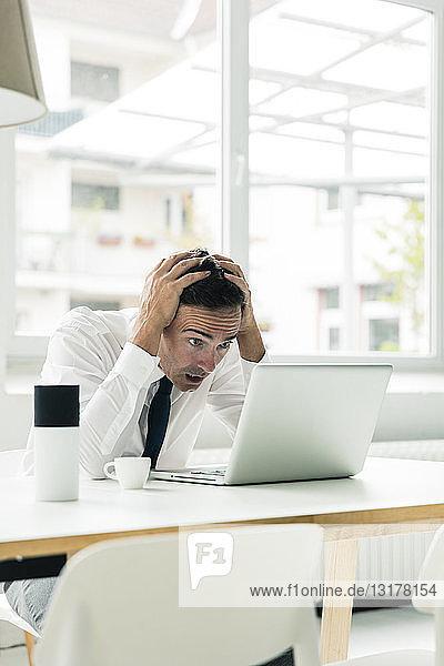 Geschockter Geschäftsmann schaut auf Laptop auf Tisch im Büro