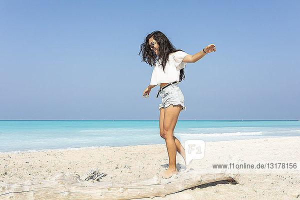 Junge Frau am Strand beim Balancieren auf einem Baumstamm