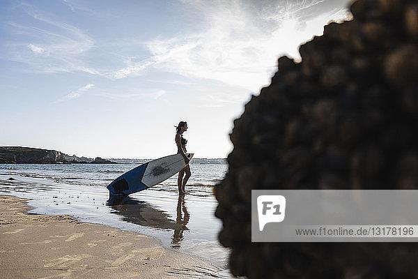 Frankreich  Bretagne  junge Frau mit Surfbrett am Meer stehend