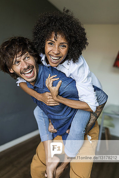 Cheerful man carrying girlfriend piggyback at home