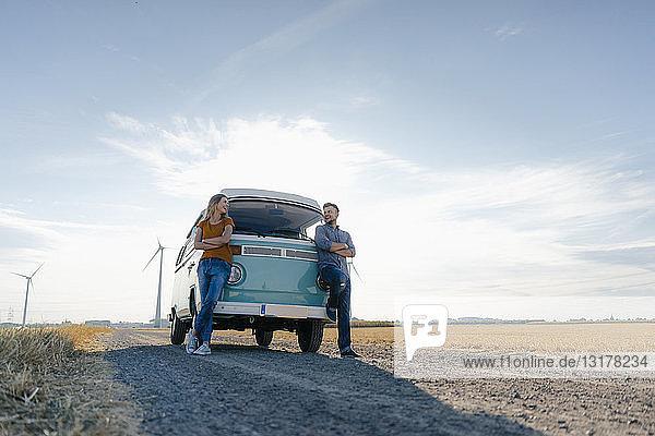 Glückliches Paar steht am Wohnmobil in ländlicher Landschaft