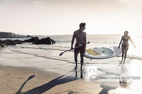 Frankreich,  Bretagne,  junges Paar mit einem SUP-Board gemeinsam auf See