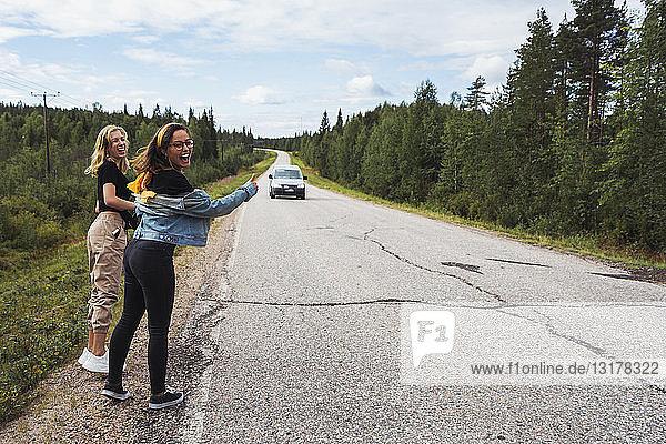 Finnland  Lappland  zwei glückliche Frauen trampen auf der Landstraße