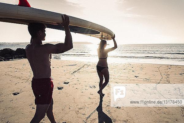 Frankreich  Bretagne  junges Paar mit einem SUP-Board gemeinsam am Strand