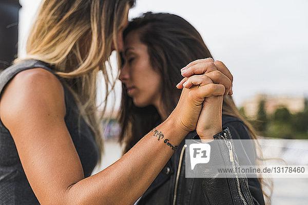 Zärtliches lesbisches Paar  das im Freien Händchen hält
